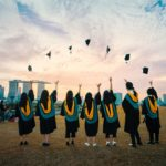 college graduates throwing hats into the air