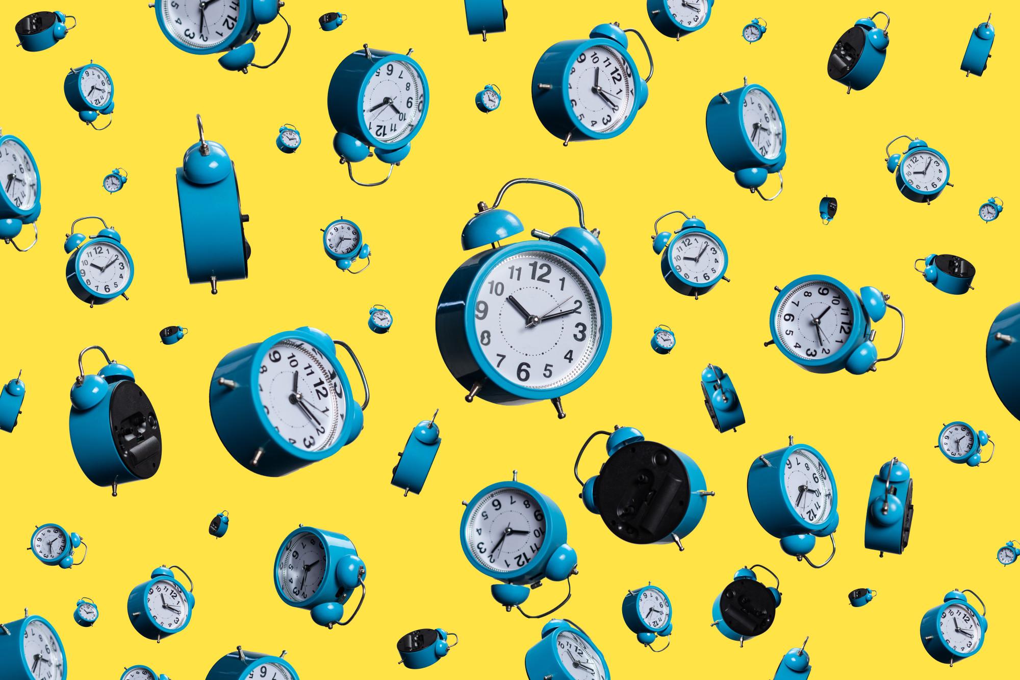 alarm clocks on yellow background