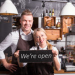 business owners with open sign
