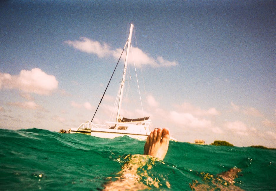Person Swimming with a Yacht in the Background