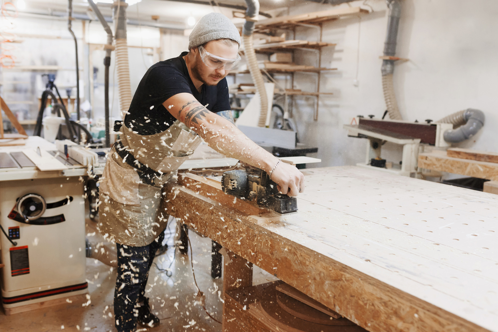 Carpenter Working with Electric Planer on Wooden Plank